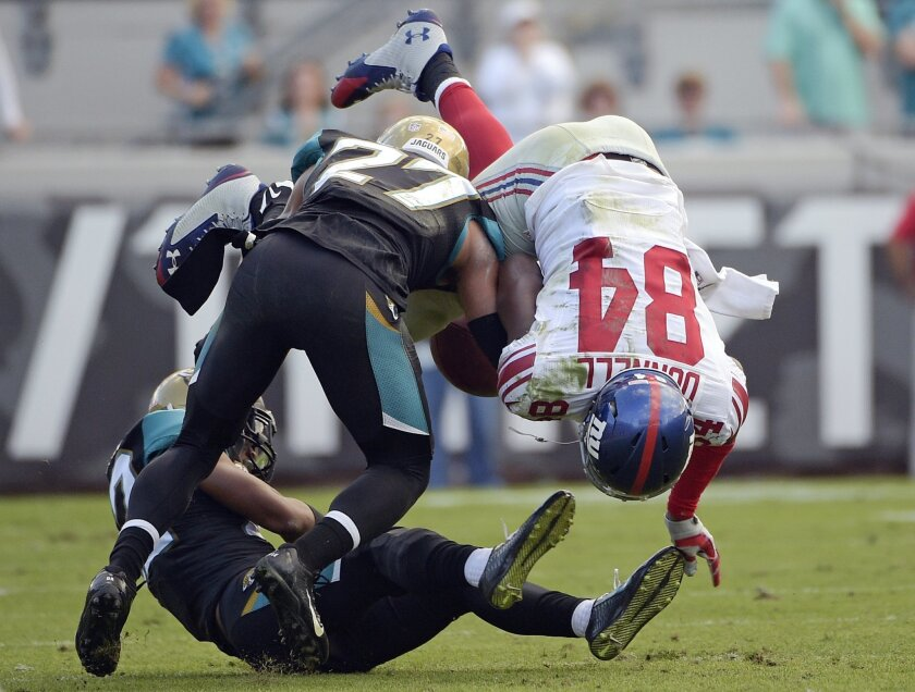 New York Giants tight end Larry Donnell (84) fumbles the ball as he is hit by Jacksonville Jaguars cornerback Dwayne Gratz (27) during the second half of an NFL football game in Jacksonville, Fla., Sunday, Nov. 30, 2014. Jacksonville recovered the fumble and Aaron Colvin returned it for a 41-yard touchdown. (AP Photo/Phelan M. Ebenhack)