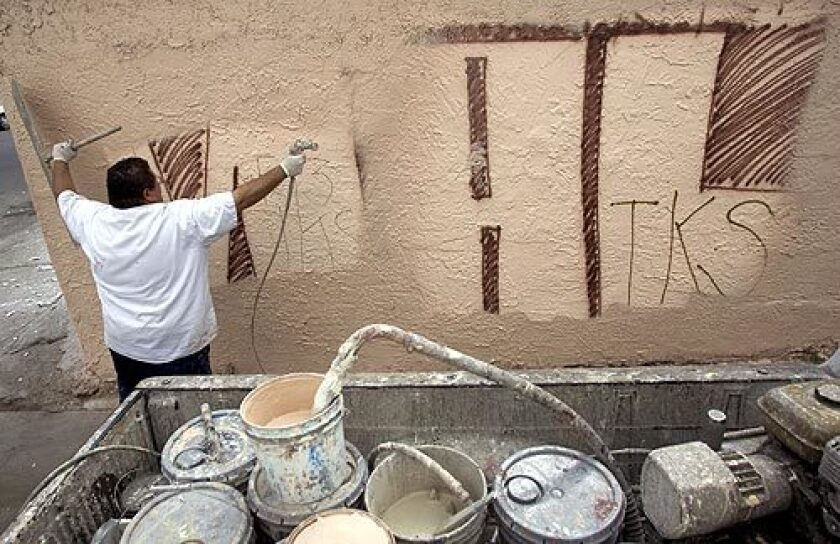 Martin Magdaleno, who works for a graffiti removal company, paints over graffiti on the side of a garage, in the Florence-Firestone area of Los Angeles County, Wednesday.