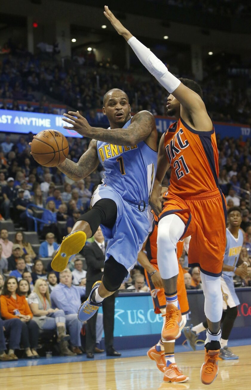Denver Nuggets guard Jameer Nelson (1) passes around Oklahoma City Thunder guard Andre Roberson (21) in the first half of an NBA basketball game in Oklahoma City, Sunday, Nov. 1, 2015. (AP Photo/Sue Ogrocki)