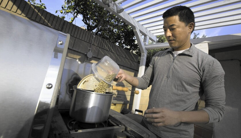 Los Angeles Times reporter Jason Song pours green coffee beans in a popcorn popper to roast on his patio BBQ grill at his home in South Pasadena.
