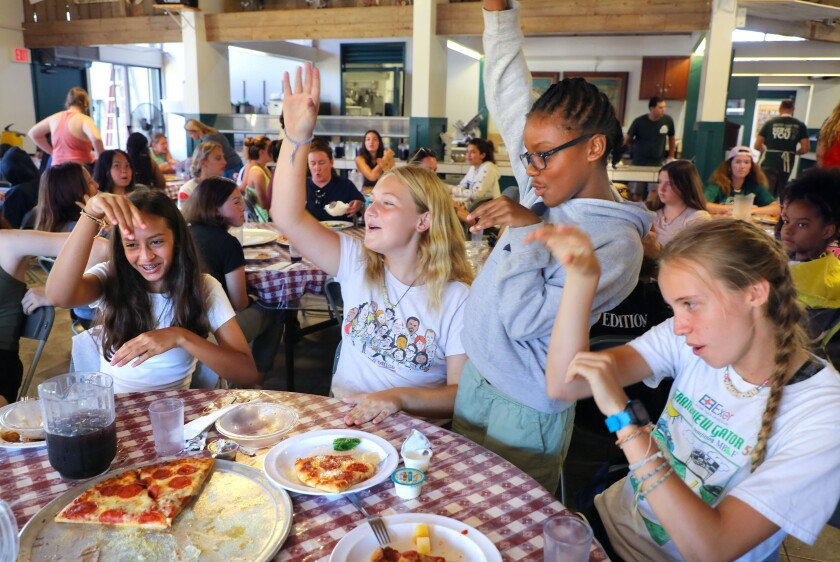 Experience Camp participants joke around during lunch in the dining hall on Wednesday at Green Oak Ranch in Vista. The campers are, from left, Alina Sendowsky, 14, of Orange County, Brooke Kinney, 14, of Orange County, Parker Allen, 10, of Los Angeles, and Heather Jensen, 14, of Manhattan Beach. The free weeklong camp serves youth who have experienced the death of a family member or caregiver.