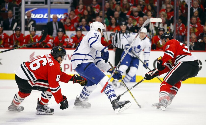 Chicago Blackhawks left wing Teuvo Teravainen (86) loses his stick as Toronto Maple Leafs defenseman Jake Gardiner (51) and Blackhawks defenseman Michal Rozsival (32) battle for the puck during the first period of an NHL hockey game on Monday, Feb. 15, 2016, in Chicago. (AP Photo/Jeff Haynes)