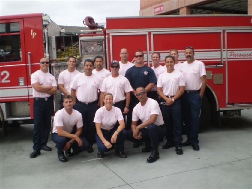 Firefighters at Station 12 on Imperial Avenue showed support Tuesday for a colleague recently diagnosed with breast cancer by wearing pink T-shirts. One is wearing a navy blue T-shirt that has pink letters.