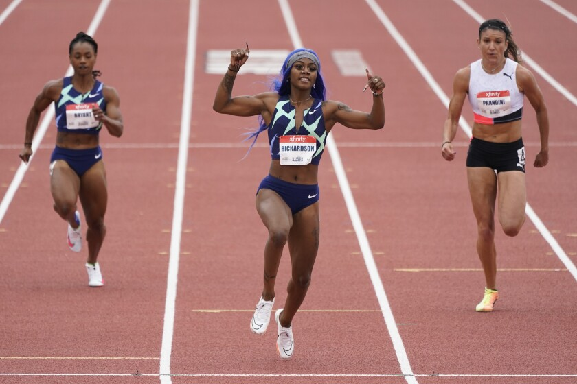 Sha'Carri Richardson gives thumbs up during women's 100-meter dash while two other women run on either side behind her