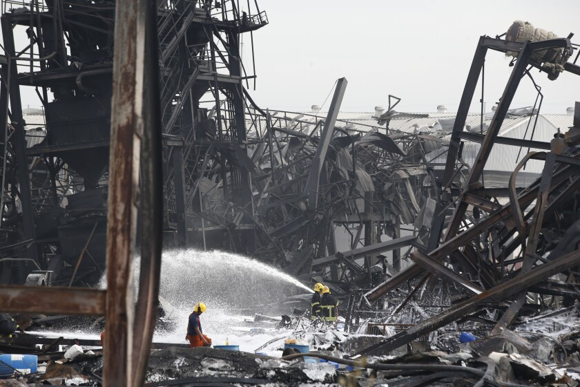 Firefighters spray foam amid twisted metal frames of a charred chemical factory Tuesday, July 6, 2021 in Samut Prakan, Thailand.Firefighters finally extinguished a blaze at a chemical factory just outside the Thai capital early Tuesday, more than 24-hours after it started with an explosion that damaged nearby homes and then let off a clouds of toxic smoke that prompted a widespread evacuation. (AP Photo/Anuthep Cheysakron)