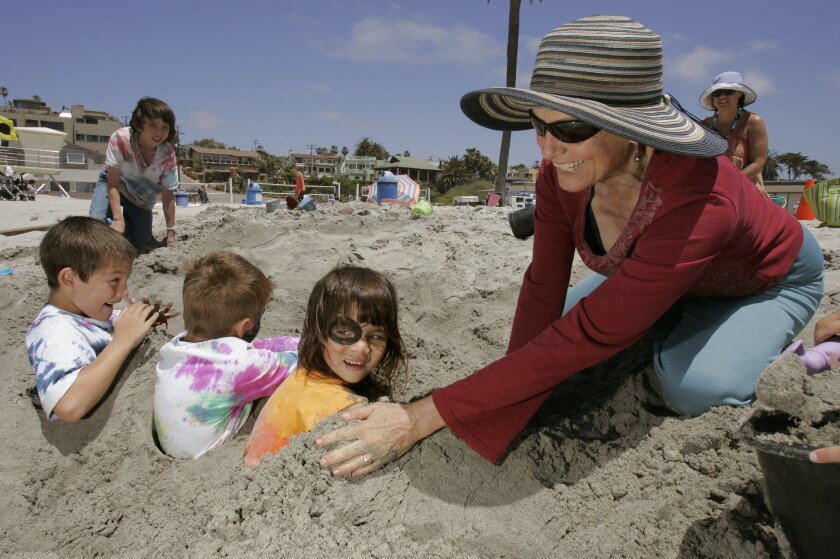 Karen Haskins buries her daughter Mikaela, 5, at Moonlight State Beach during a last day of school beach outing for Mikaela and her classmates from Innovation Centre Charter School in Encinitas.