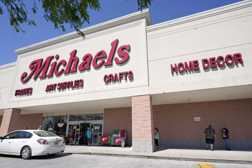 FILE - In this April 24, 2020 file photo, customers lineup outside a Michaels store in Houston. The arts and crafts retailer is going private. The Irving, Texas-based retail chain said Wednesday, March 3, 2021, it has agreed to be acquired by Apollo Global Management in a $5 billion deal. (AP Photo/David J. Phillip, File)