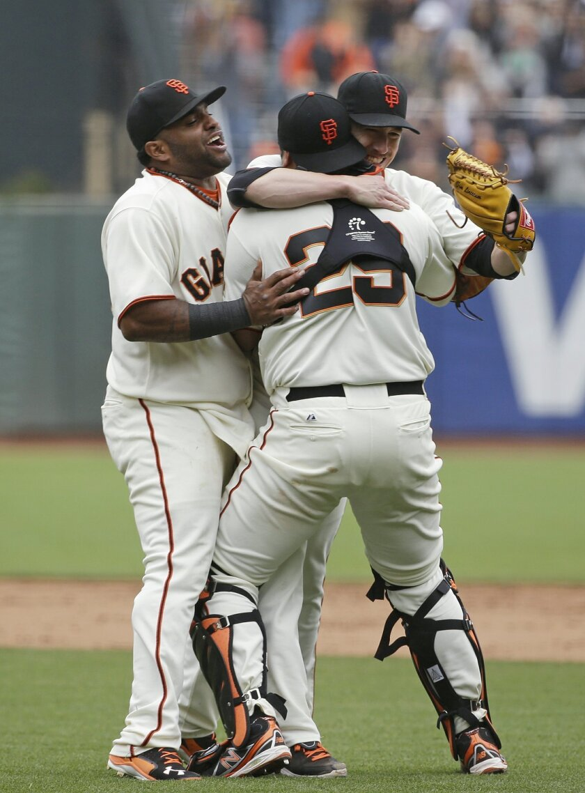 Giants pitcher Tim Lincecum embraced by catcher Hector Sanchez and third baseman Pablo Sandoval after no-hitter in 2014.