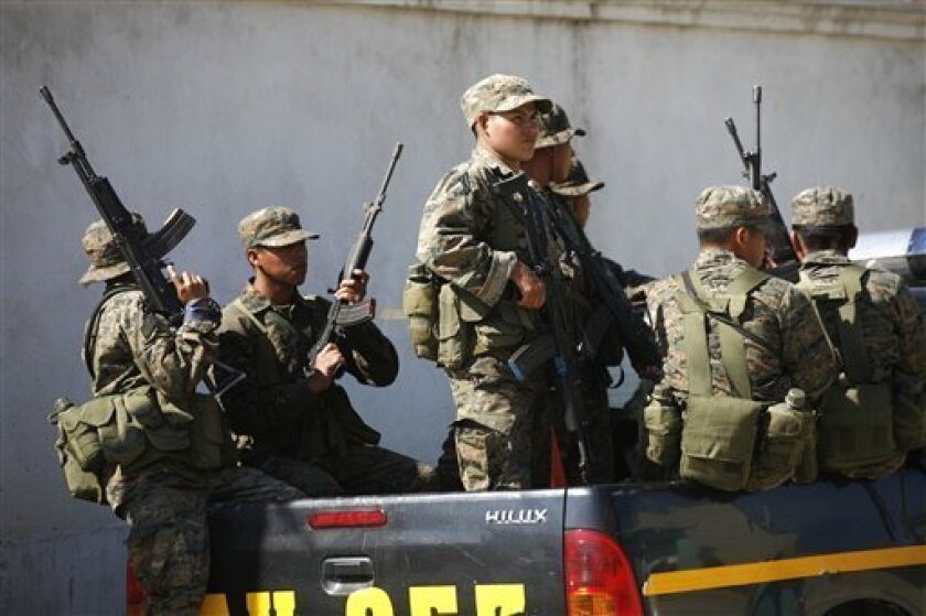 FILE - In this Dec. 21, 2010 file photo, soldiers stand guard while police raid a home in Coban, Guatemala. In Dec. 2010, the Guatemalan military declared a month long state of siege in Alta Verapaz in hopes of reclaiming cities that have been taken over by Mexico's Zetas drug gang. Guatemalan authorities say they have begun to see new and disturbing evidence of an alliance between the Mara Salvatrucha street gang and the Zetas drug cartel, one of the most feared criminal organizations in Latin America, a deal with the potential to further undermine the U.S.-backed effort to fight violent crime and narcotics trafficking in the region. (AP Photo/Rodrigo Abd, File)