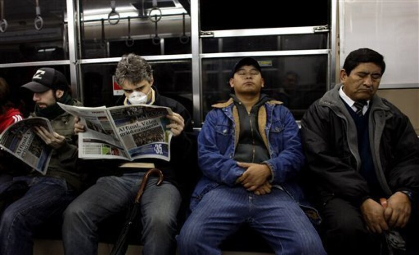 Passengers, one wearing a face mask as a precaution against swine flu contagion, ride a subway train in Buenos Aires, Monday, July 6, 2009. (AP Photo/Natacha Pisarenko)