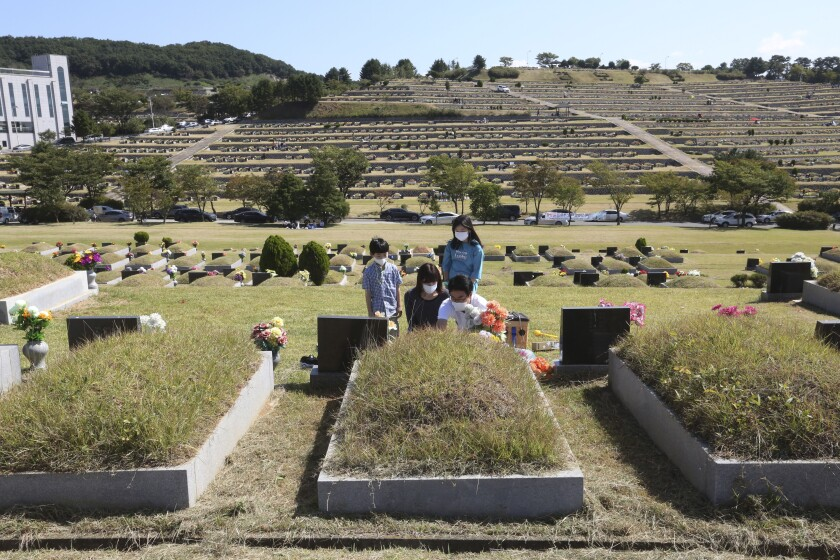 A family gathers at a grave in a cemetery.