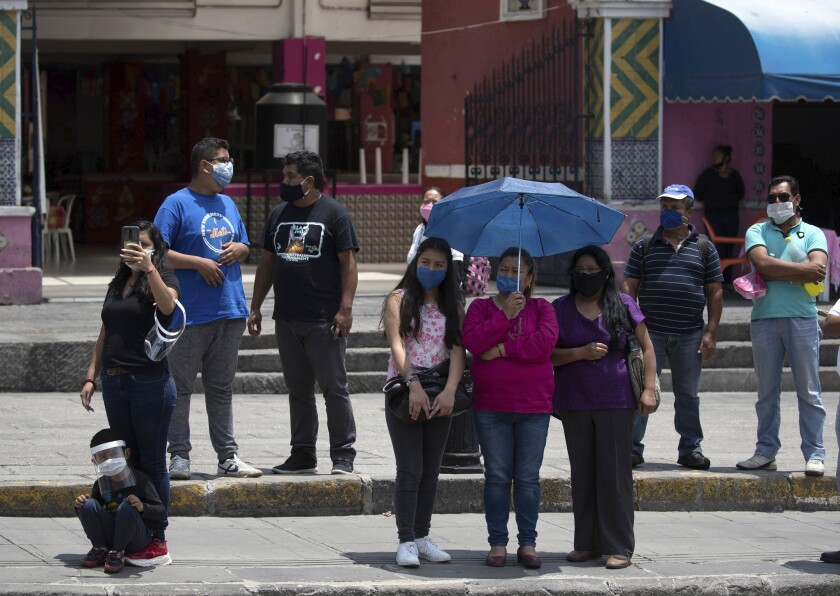 Relatives of Mexican citizens that died from COVID-19 complications in the United States attend a ceremony for their loved ones in Puebla, Mexico, Monday, July 13, 2020. (AP Photo/Fernando Llano)