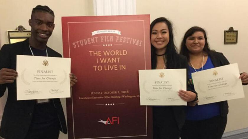Los estudiantes de cine Jevonne Davis, Leanne Elizabeth Caldeión y Angel Marie Velásquez muestran sus certificados en la Casa Blanca.