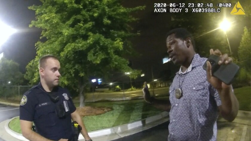 This screen grab taken from body camera video provided by the Atlanta Police Department shows Rayshard Brooks speaking with Officer Garrett Rolfe in the parking lot of a Wendy's restaurant, late Friday, June 12, 2020, in Atlanta. Rolfe has been fired following the fatal shooting of Brooks and a second officer has been placed on administrative duty. (Atlanta Police Department via AP)