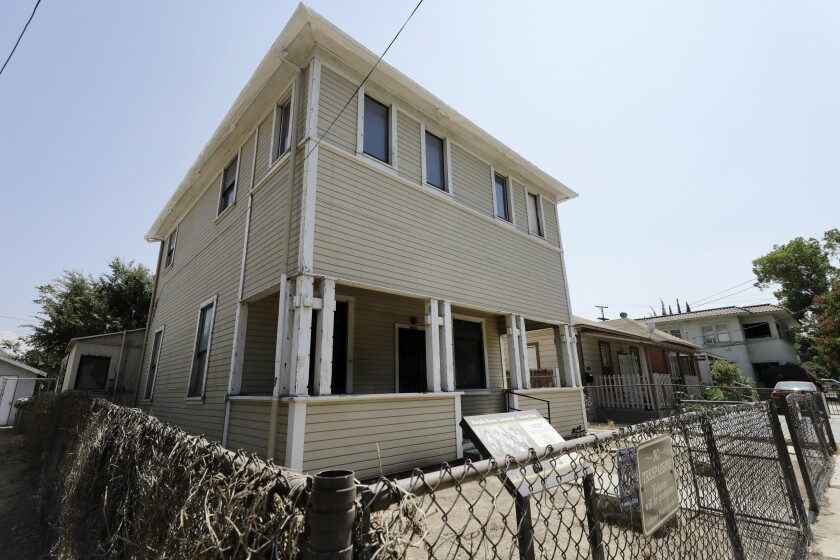 The modest two-story Harada House, surrounded by a chain-link fence.