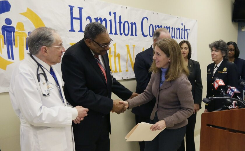 U.S. Department of Health and Human Services Secretary Sylvia Burwell meets with Hamilton Community Health Network Chief Medical Officer, Dr. Michael Giacalone Jr., left, and CEO Clarence Pierce, after addressing the media, Thursday, Feb. 18, 2016, in Flint, Mich. The secretary announced $500,000 i