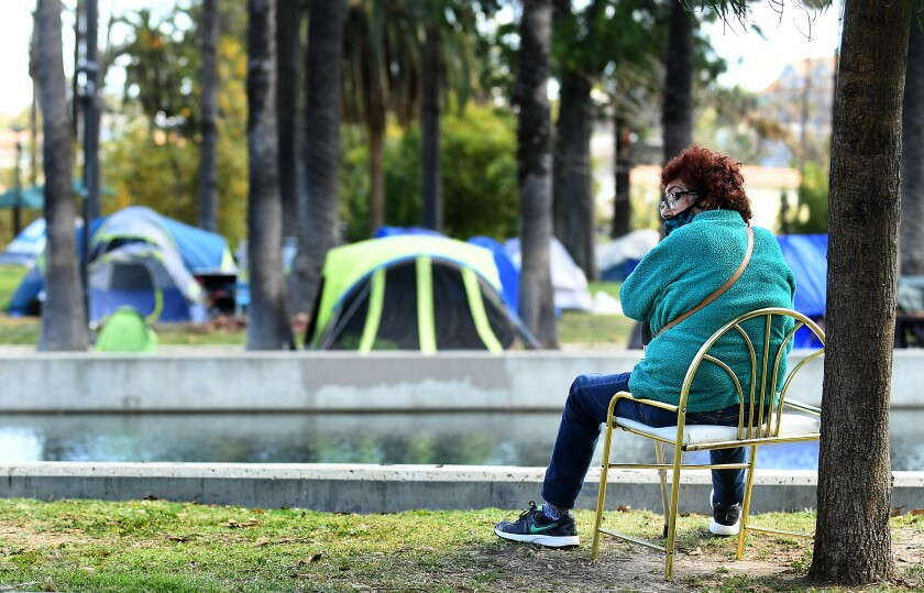 A woman sits in Echo Park as tents that are part of a large homeless encampment sit by the lake.