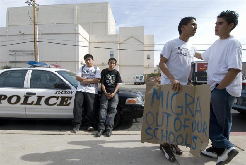 Vista de unos jóvenes hispanos junto a una patrulla de la policía de Tucson. EFE/Archivo