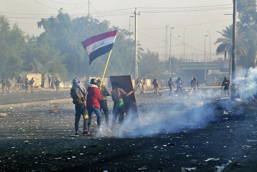 Protesters wave the national flag as security forces fire tear gas during an ongoing protest in Baghdad.