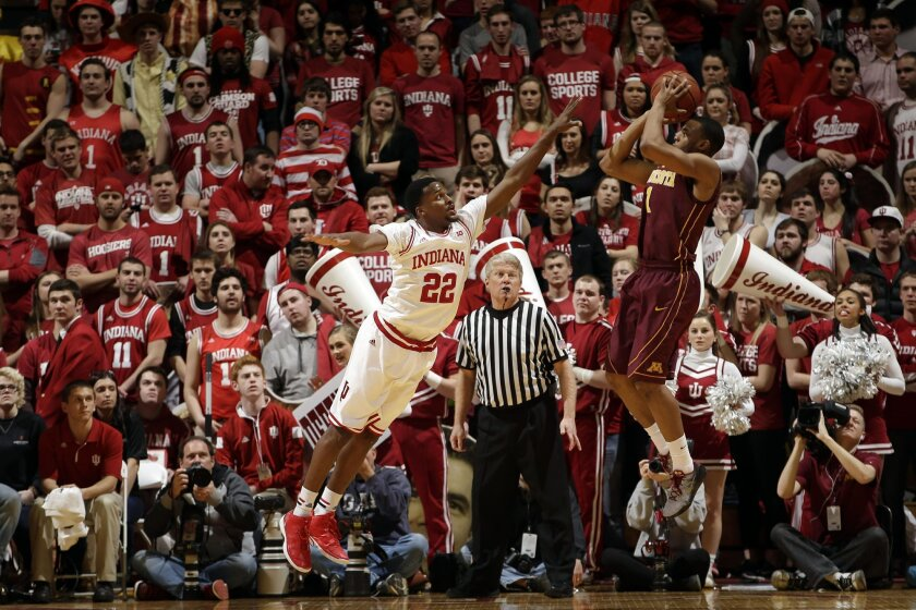 Minnesota guard Andre Hollins, right, shoots over Indiana guard Stanford Robinson in the second half of an NCAA college basketball game, Sunday, Feb. 15, 2015, in Bloomington, Ind. Indiana won 90-71. (AP Photo/AJ Mast)