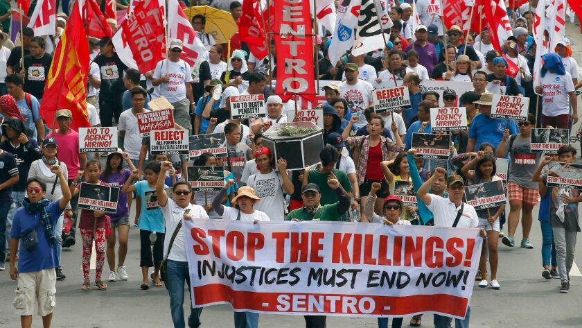 Protesters in Manila on May 1 carry a mock coffin to protest the continuing killings under Philippin