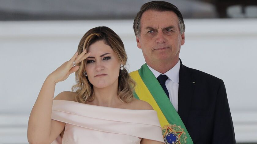 With her husband, Brazil's new President Jair Bolsonaro in the background, Brazil's new first lady M