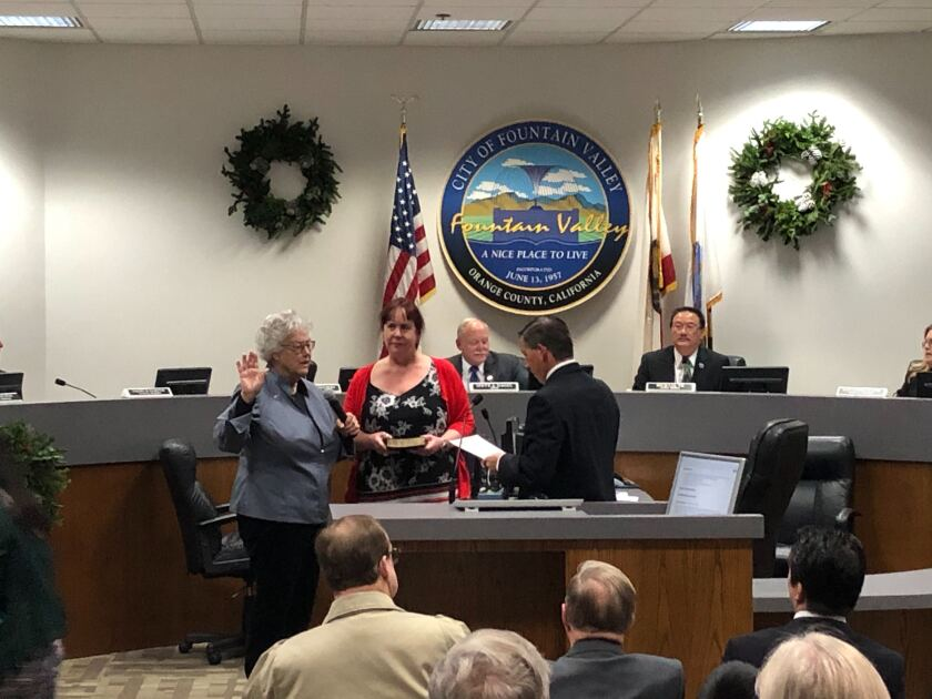 Cheryl Brothers was sworn in with her right hand raised in front of the dais. Her daughter holds bible she when Brothers' left hand is placed on. Audience members are seen from the back in the foreground.