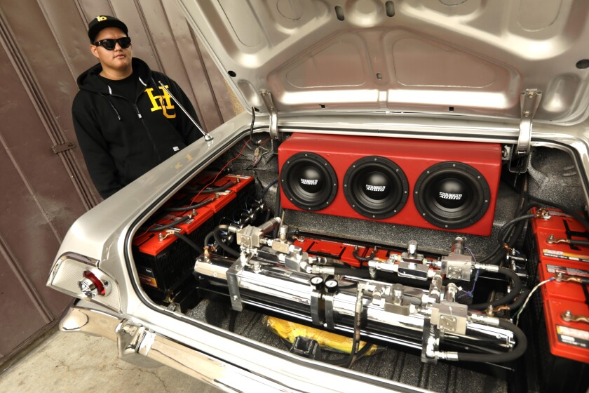 Jonathan Rodriguez, 20, stands next to his 1963 Impala SuperSport lowrider at Speedy's Metal Finishing in Long Beach.