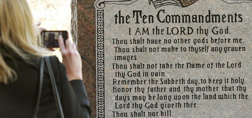 """FILE - In this Nov. 15, 2012 file photo, a woman takes a picture of a granite monument engraved with the Ten Commandments after it was erected on the north side of the state Capitol grounds in Oklahoma City. The word """"Sabbath"""" was misspelled on the monument. An attempt by a group of New York-based Satanists to erect a monument to the devil on the Capitol steps drew a bitter reaction on Monday from residents who say such a statue is not welcome. Officials with The Satanic Temple maintain Oklahoma opened the door for such a display when it authorized a Ten Commandments monument several years ago. (AP Photo/The Oklahoman, Jim Beckel, File) LOCAL TV OUT; LOCAL INTERNET OUT; EDMOND SUN OUT, OKLAHOMA GAZETTE OUT; TABLOIDS OUT"""
