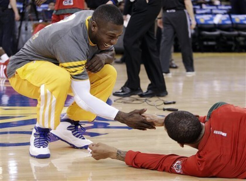 Golden State Warriors' Nate Robinson, left, shakes hands with his former teammate, Milwaukee Bucks' Monta Ellis, prior to the their NBA basketball game, Friday, March 16, 2012, in Oakland, Calif. (AP Photo/Ben Margot)