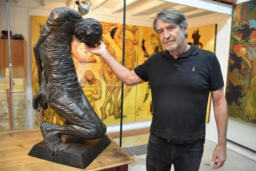 """El escultor y pintor Mark Strickland posa junto a su estatua en bronce """"Sacrificio del abuelo"""" el 26 de septiembre de 2017, en su estudio en Sierra Madre, California (EE.UU.). Las esculturas que representan a un anciano encorvado, una joven desnuda y la cabeza de la Estatua de la Libertad son tres obras con reminiscencias latinas que sirven al artista Mark Strickland para """"documentar el sufrimiento"""" que vive la población inmigrante en EEUU. EFE"""
