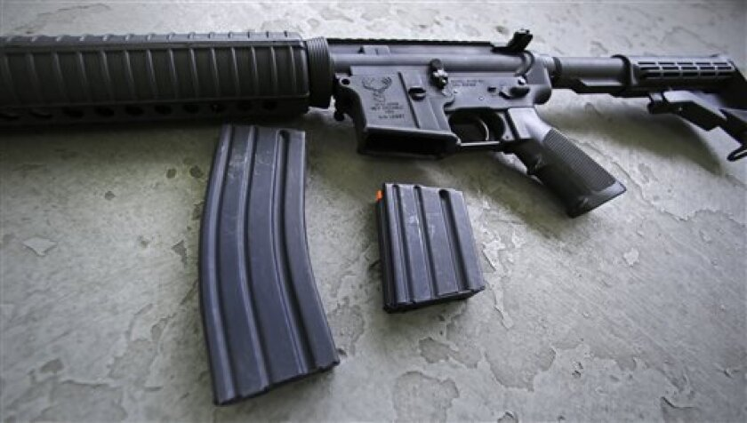 A 30 round magazine, left, and a 10 round magazine, right, rest below an AR-15 rifle at the Ammunition Storage Component company in New Britain, Conn., Wednesday, April 10, 2013.
