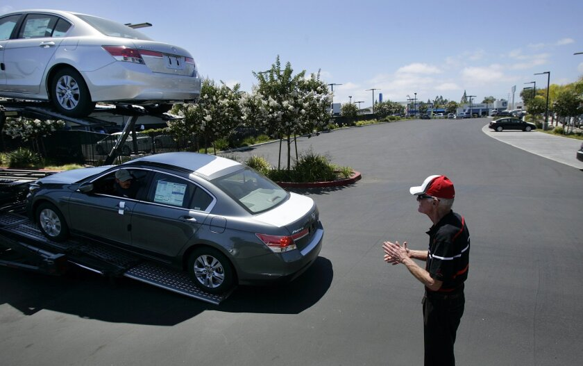J.P. Bo, senior salesman at Pacific Honda watches as nine cars are delivered to the dealership.