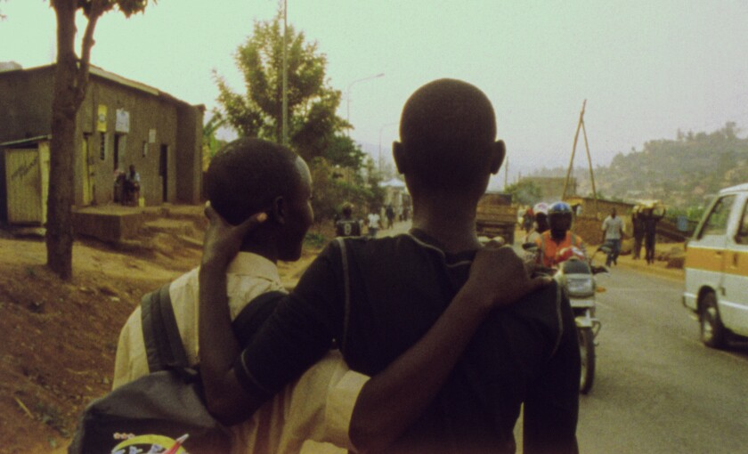 Two young men with their arms around each other walk down a street