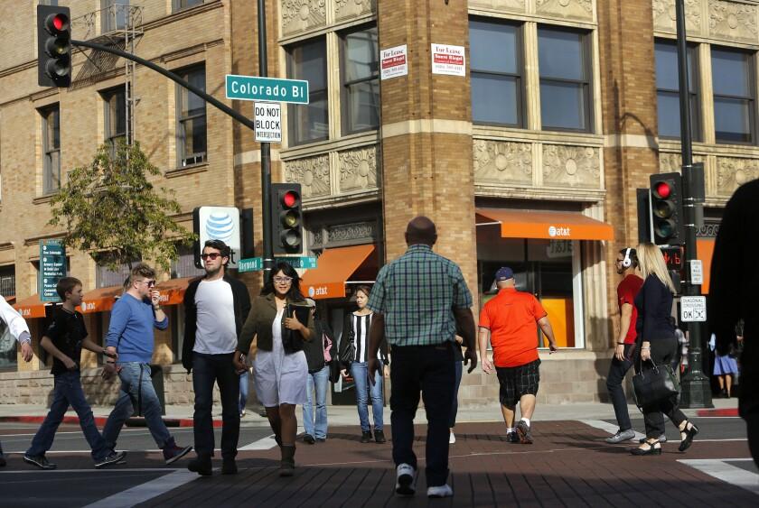 Pedestrians cross Colorado Boulevard in Pasadena. Walkable neighborhoods in older suburbs of Los Angeles are seeing increasing development, a new study says.