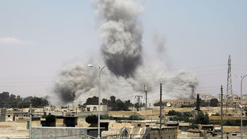 Smoke billows from buildings in the northern Syrian city of Raqqah on June 18, 2017. U.S.-backed fighters are trying to drive Islamic State from its self-declared capital.