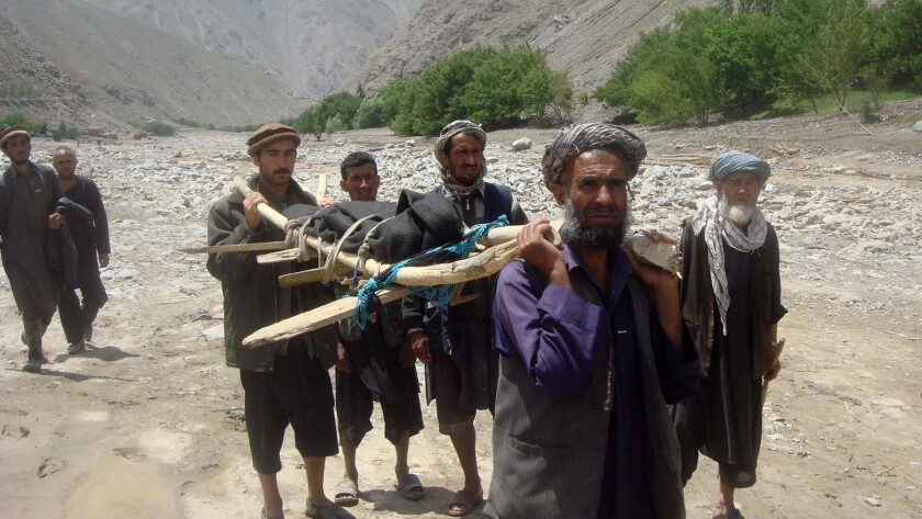 Afghan villagers carry the body of a flood victim in the Guzargah-e-Nur district of Baghlan province.