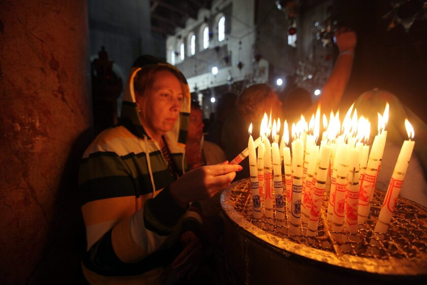 A woman lights candles in the Church of the Nativity in the West Bank city of Bethlehem, where tradition says Jesus was born. The city will be added to the itineraries of Viking Ocean Cruises.