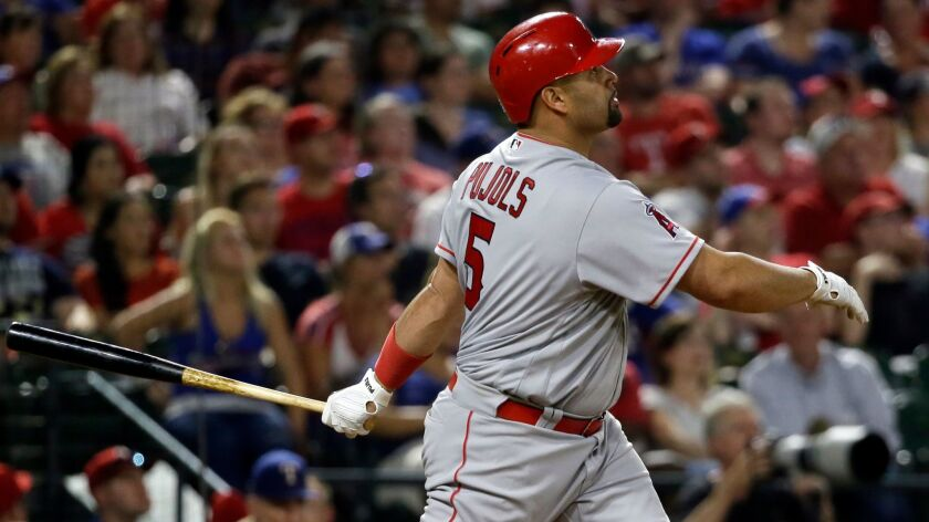 Los Angeles Angels' Albert Pujols follows through on a three-run home run swing off a pitch from Tex