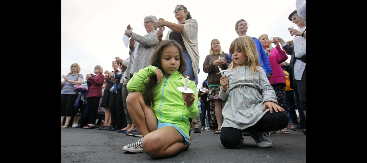 Ava Ramirez, left, and Availa Dawsey-Richardson, both 4, hold candles during an interfaith vigil for immigrant families that have been separated at the border.