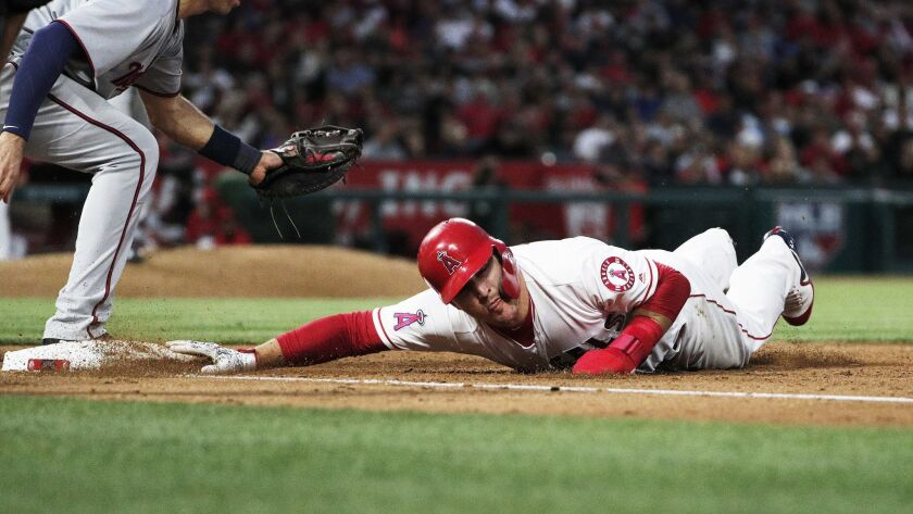 ANAHEIM, CA - MAY 12, 2018: Los Angeles Angels center fielder Mike Trout (27) dives back to first b