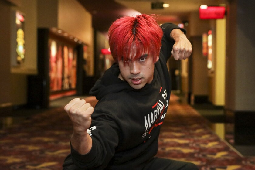 A man with red hair poses with his hands in fists.