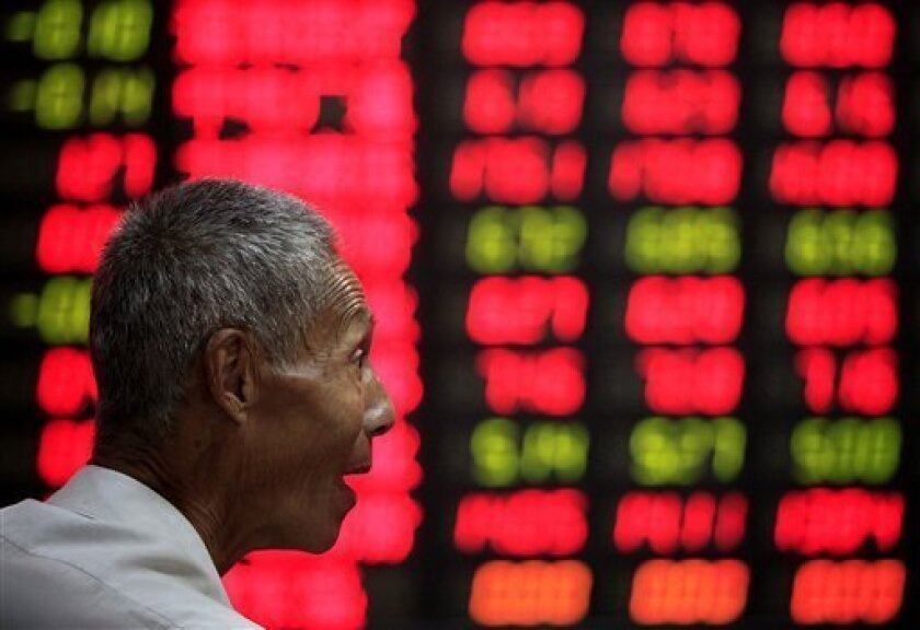 An investor chats with another as he looks at the stock price monitor at a private securities company Thursday July 2, 2009 in Shanghai, China. Chinese shares rose Thursday on optimism about a possible economic rebound, led by resource shares following a hike in state-set fuel prices. The benchmark Shanghai Composite Index jumped 52.1 points, or 1.7 percent, to close at 3060.25. (AP Photo/Eugene Hoshiko)