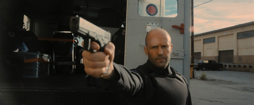 Jason Statham points a gun while protecting an armored truck.