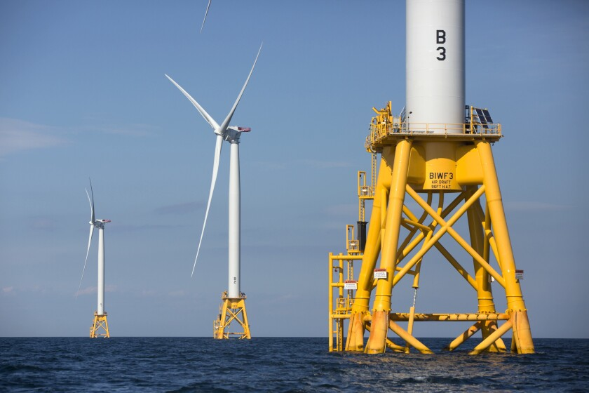 Three white wind turbines on yellow platforms in the ocean