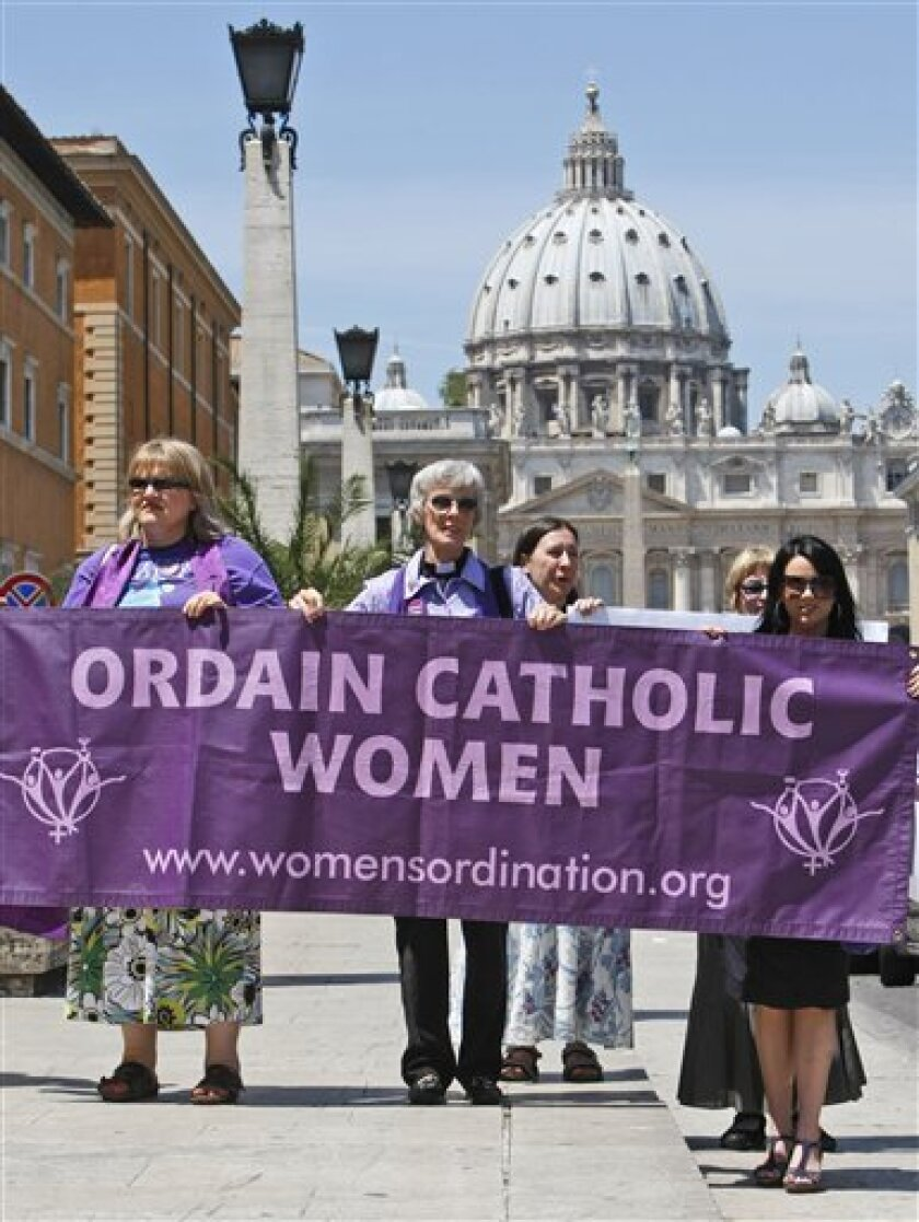 Representatives of the Women's Ordination Conference stage a protest in front of St.Peter's Basilica, in Rome, with holding poster at front, from left, Therese Koturbash from Dauphin, Matitoba, Canada, Mary Ann Schoettly from Newton, N.J, US, and Erin Saiz Hanna, Washington, D.C. US, as they protest on Tuesday, June 8, 2010. Groups that have long demanded that women be ordained Roman Catholic priests took advantage of the Vatican's crisis over clerical sex abuse to press their cause demanding the Vatican open discussions on letting women join the priesthood. (AP Photo/Pier Paolo Cito)