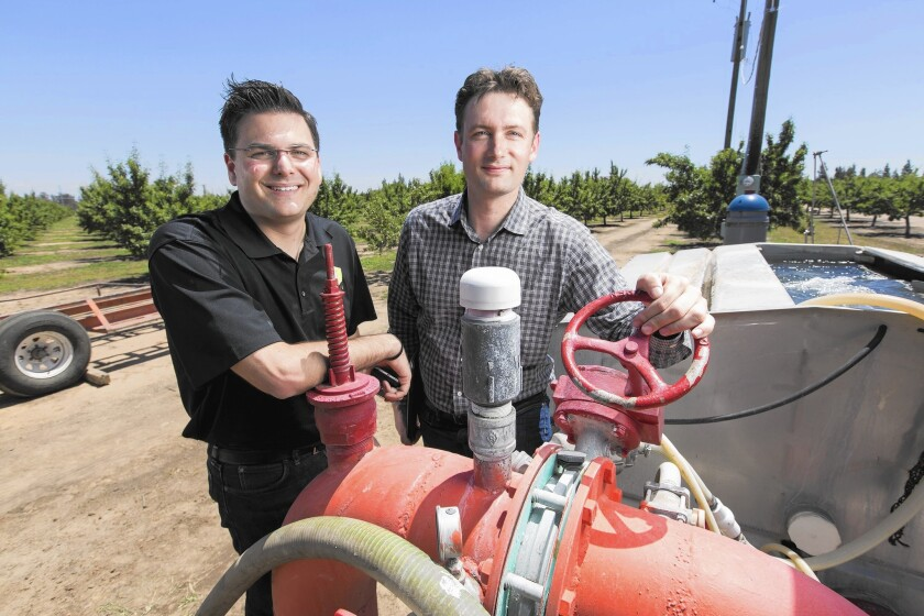 Vincent Ricchiuti, left, of P-R Farms and Olivier Jerphagnon of PowWow Energy stand next to a well that Jerphagnon's firm is monitoring to facilitate precise irrigation of an almond orchard in Fresno.