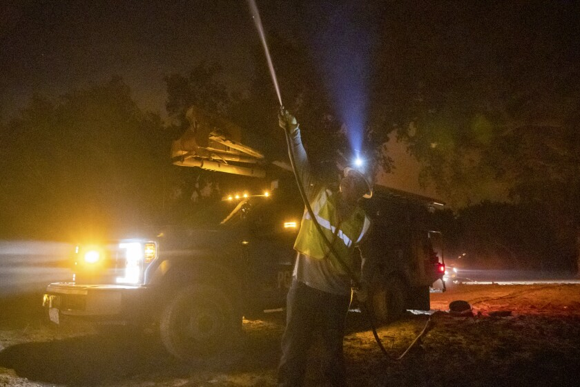 PG&E employee sprays water on burning telephone pole