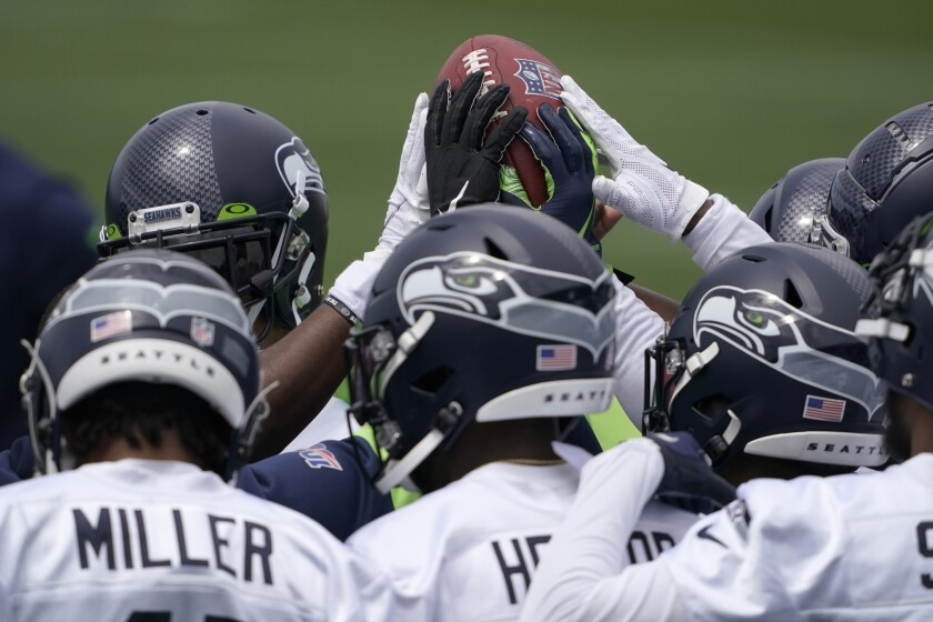 Seattle Seahawks defensive players touch the football during a huddle at NFL football practice Tuesday, June 15, 2021, in Renton, Wash. (AP Photo/Ted S. Warren)