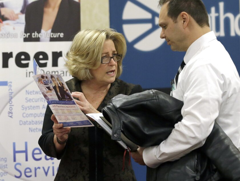 FILE - In this Wednesday, Jan. 22, 2014 file photo, recruiter Valera Kulow, left, speaks with job seeker Leonardo Vitiello during a career fair in Dallas. The Labor Department reports the number of people who applied for unemployment benefits last week on Thursday, June 5, 2014. (AP Photo/LM Otero, File)